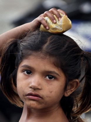 10 January 2012: An Indian child carries a plastic pouch containing food in Hyderabad, India