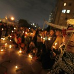 An Egyptian protester wearing a flower in his headband attends a candlelight vigil honoring those killed by security forces one year ago during the 18-day uprising that ousted President Hosni Mubarak. (AP Photo/Khalil Hamra)