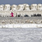 A child runs past a wave protection dam covered in ice as the waters of the Black Sea are frozen near the shore in Constanta, Romania: the weather is so cold that some areas of the sea have frozen near the coastline. (AP Photo/Vadim Ghirda)