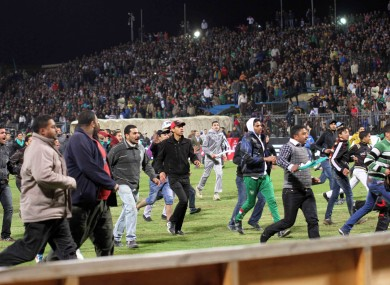 Egyptian fans rush into the field following Al-Ahly club soccer match against Al-Masry club at the soccer stadium in Port Said