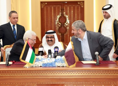 Palestinian President Mahmoud Abbas, left, shakes hands with Khaled Mashaal, right, as the Emir of Qatar looks on following the 6 Feb deal signing.