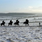 Racehorses work out on the snowy gallops in Malton, North Yorkshire.