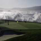 Greenskeepers look on as waves crash over the seawall on the 18th hole of the Pebble Beach Golf Links.
