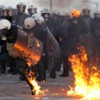 A riot police officers tries to extinguish flames from a petrol bomb thrown by protestors outside the Greek parliament, Athens. (AP Photo/Thanassis Stavrakis)