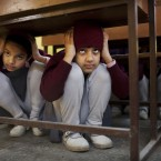 Indian schoolgirls lie low under their desks during a disaster drill checking the alertness and preparedness of various agencies in the event of a major earthquake in New Delhi, India. (AP Photo/Kevin Frayer)