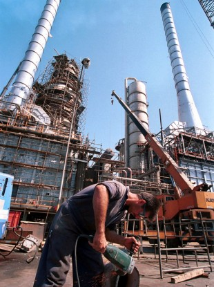 File photo shows an Iranian oil worker repairs a pipe at an oil refinery in Tehran