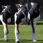 New York Yankees' Phil Hughes, from left, Boone Logan and CC Sabathia stretch during practice at baseball spring training. (AP Photo/Matt Slocum)