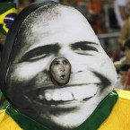 A performer from the Uniao da Ilha samba school parades carrying a costume with a photo of former soccer player Ronaldo during carnival celebrations. (AP Photo/Silvia Izquierdo)