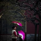 A Chinese woman performs morning exercise with fans at the Ditan park in Beijing, China, Wednesday, Feb. 29, 2012. (AP Photo/Andy Wong)
