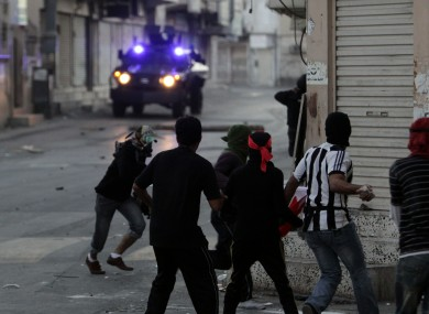 Protesters throw stones at armoured vehicles in the streets of Sanabis, on the edge of Manama, yesterday.