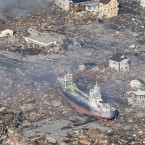 A large vessel is seen stranded among ruins in Kesennuma, Miyagi Prefecture a day after the tsunami struck. (Kyodo/PA Images)