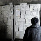 Checking messages for families and friends posted on a board at an evacuation shelter in Ofunato, Iwate Prefecture the day after the earthquake and tsunami. (Kyodo/PA Images)