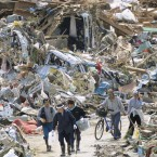 People walk through debris in Rikuzentakata, Iwate Prefecture, northeastern Japan, two days after the massive earthquake and tsunami destroyed the city. (Kyodo/PA Images)