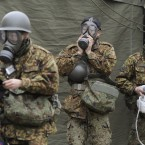 Members of Japan's self-defence forces wear protective gear and prepare for radioactive decontamination in Nihommatsu, Fukushima Prefecture on 15 March, 2011, after high levels of radiation were detected in the area. (Kyodo/PA Images)