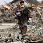 Ritsuko Oikawa, 84, walks in the rubble towards the ruins of her house in Rikuzentakata, Iwate Prefecture. (AP Photo/Shizuo Kambayashi/PA Images)