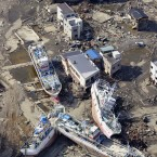 This photo taken one month after the disasters shows Kesennuma, Miyagi Prefecture, where ships remain abandoned on land after being swept ashore. (Kyodo/PA Images)