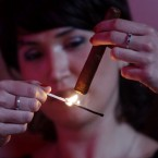 A woman lights her cigar at the annual cigar festival gala dinner in Havana, Cuba. (AP Photo/Javier Galeano)