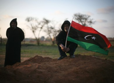 Libyan men, one waving a pre-Gaddafi flag, attend a funeral in Benghazi on Monday