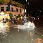 In this photo taken on Wednesday, March 7, 2012, a motorist drives through a flooded road in Kuala Lumpur, Malaysia. (AP Photo)