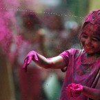 An Indian girl has her face smeared with colored powder during the festival of Holi. (AP Photo/Arun Sankar K.)