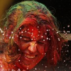 An Indian women, her face smeared with colored powder, reacts as water is squirted on her during Holi celebrations in Chennai, India. (AP Photo/Arun Sankar K.)