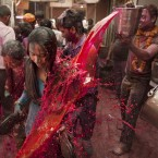 A Hindu devotee has a bucket of coloured water poured on her whilst walking to the the Banke Bihari temple. (AP Photo/Kevin Frayer)