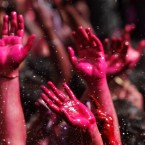 Colored hands are seen as water is sprayed on people during Holi celebrations in Allahabad, India. (AP Photo/Rajesh Kumar Singh)