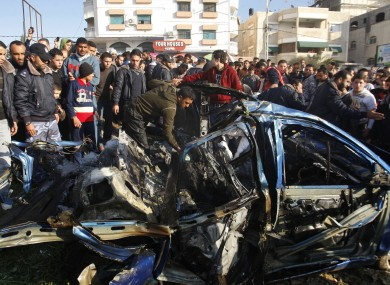 Palestinians gather around the wreckage of a car targeted in the airstrike that killed Zuhair al-Qaissi