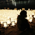 A young boy walks past lanterns placed at the shore in Tokyo Bay to mark the first anniversary of the earthquake and tsunami which devastated northeast Japan. (AP Photo/Greg Baker)