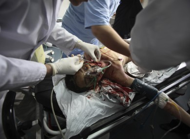 Palestinian medics treat a wounded person at Shifa hospital following an Israeli air strike, in Gaza City, Monday, March 12, 2012