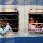 Passengers looks out from a moving train in New Delhi, India. (AP Photo/Tsering Topgyal)
