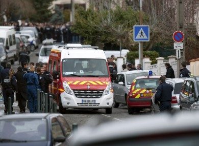 Police officers and firefighters gather at the site of a shooting in Toulouse