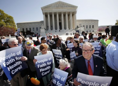 Protesters in favour of health care reform demonstrate outside of the Supreme Court in Washington today.