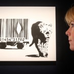 A Bonham's employee looks at Banksy's Leopard and Barcode, estimated to fetch an estimate of £60,000 - £80,000 at Urban Art. (Lewis Whyld/PA Images)
