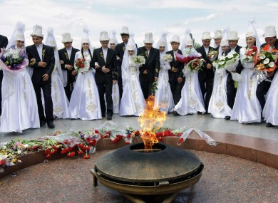 Kyrgyz couples lay flowers by the Eternal Flame in Bishkek last May before a mass wedding ceremony.