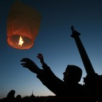 A man launches a paper lantern during a ceremony to mark Earth Hour at Palace Square in St Petersburg, Russia. (AP Photo/Dmitry Lovetsky)
