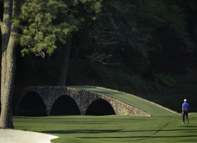 iger Woods walks towards the Ben Hogan Bridge on the 12th fairway during a practice round for the Masters.