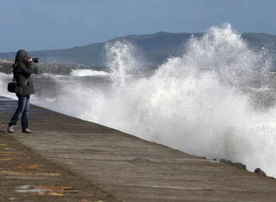 A woman photographs waves as they crash against the sea wall at Howth Pier in Dublin on Wednesday