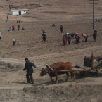 North Korean farmers, working in a field, are seen through the window of a train heading to North Phyongan Province, about 50 kilometers south of the border town of Sinuiju along North Korea's west coast last week. (AP Photo/Ng Han Guan)