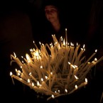 A Christian worshipper lights candles inside the Church of the Holy Sepulchre, traditionally believed to be the burial site of Jesus Christ, in Jerusalem's Old City. (AP Photo/Sebastian Scheiner)