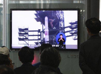 South Koreans watch a TV news program which shows North Korea's Unha-3 rocket at Seoul train station