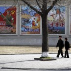 North Korean residents walk past billboards in Pyongang (AP Photo/Ng Han Guan)