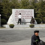 A North Korean woman cleans up calligraphy on a commemorative plaque in honor of late President Kim Il Sung in Pyongyang during the week (AP Photo/Ng Han Guan)