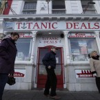 People walk past a shop in Cobh on the first stop of the MS Balmoral Titanic memorial cruise ship (AP Photo/Lefteris Pitarakis)