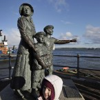 A girl plays in front of a monument for the Irish immigrants to the United States, as she and her family waits in Cobh to greet disembarking passengers of the MS Balmoral Titanic memorial cruise ship at its first stop on Monday (AP Photo/Lefteris Pitarakis)