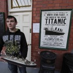 A man poses with a model of the Titanic in front of a poster as he waits to greet the disembarking passengers of the MS Balmoral Titanic memorial cruise ship at its first stop in Cobh (AP Photo/Lefteris Pitarakis)