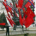 A North Korean man adjusts flags put up ahead of the Worker Party Conference to held this month in Pyongyang (AP Photo/Ng Han Guan)