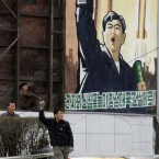 A North Korean man stands near a billboard showing a rocket launch and calling for the building of a strong and prosperous nation in Pyongyang (AP Photo/Ng Han Guan)