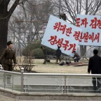 North Korean workers erect a sign paying homage to late leader Kim Jong Il and calling for the building of a