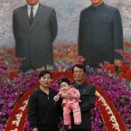 A North Korean family pose a picture in front of a picture of late leaders Kim Il Sung at left and Kim Jong Il at right during a flower show. (AP Photo/Vincent Yu)